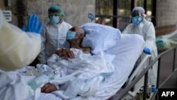 Texas ျပည္နယ္ Houston ၿမိဳ႕က ေဆးရံုတခုမွာ COVID 19 လူနာတဦးကို သယ္ေဆာင္ေနၾကတဲ့ က်န္းမာေရး ၀န္ထမ္းမ်ား။ (ဇူလိုင္ ၀၂၊ ၂၀၂၀)