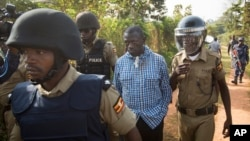 Uganda's main opposition leader Kizza Besigye, center, is arrested by police and thrown into the back of a blacked-out police van which whisked him away and was later seen at a rural police station, outside his home in Kasangati, Uganda Monday, Feb. 22, 2016.