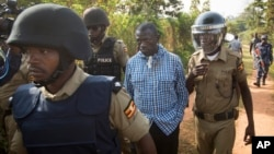 FILE - Opposition leader Kizza Besigye (C) is arrested by police outside his home in Kasangati, Uganda, Feb. 22, 2016. His laywer says the government has never been able to secure a single conviction against him.