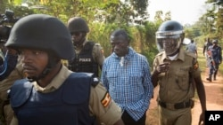FILE - Uganda's main opposition leader Kizza Besigye, center, is arrested by police and thrown into the back of a blacked-out police van which whisked him away and was later seen at a rural police station, outside his home in Kasangati, Uganda, Feb. 22, 2016.
