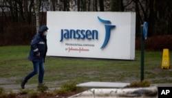 A man walks by a sign outside Johnson & Johnson subsidiary, Janssen Pharmaceutical, in Geel, Belgium, Feb. 3, 2021.