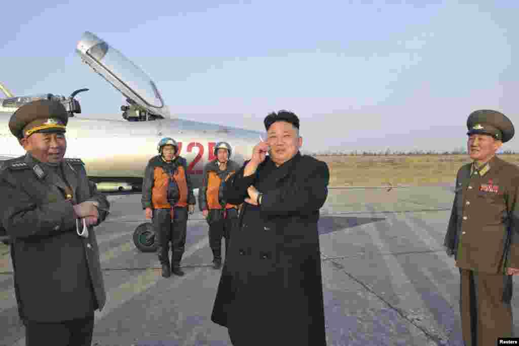 Lãnh tụ Bắc Triều Tiên Kim Jong Un hút thuốc trong lúc chờ đợi để quan sát một cuộc tập luyện của Ðơn vị Không quân 188.