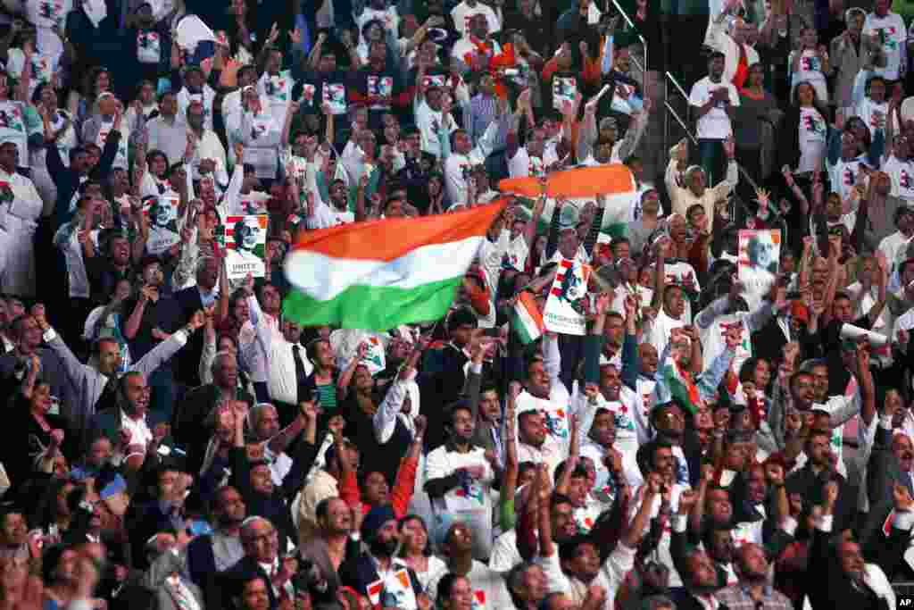 Supporters cheer and wave Indian flags as India's Prime Minister Narendra Modi gives a speech during a reception by the Indian community in honor of his visit to the United States, at Madison Square Garden, New York, Sept. 28, 2014.