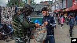 یک شبه نظامی هندی هنگام تلاشی خریطهای یک مرد کشمیری در یکی از مارکیتهای پرازدحام منطقهای سرینگر