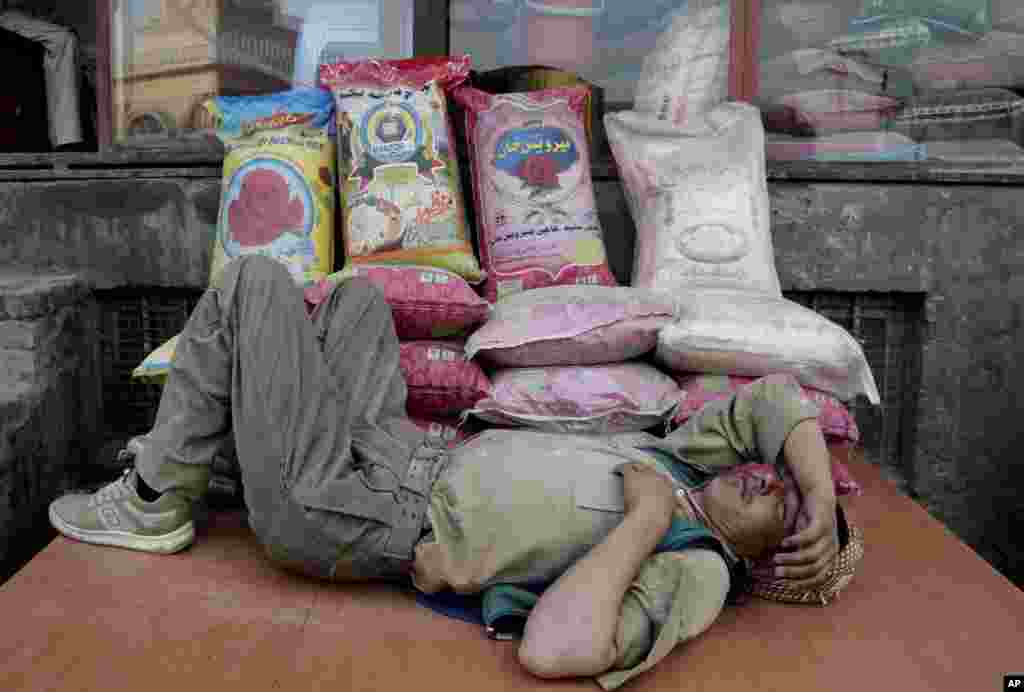 An Afghan man takes a nap while taking a break from work at a rice shop in a market in Kabul, Afghanistan.