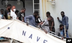 FILE - Migrants disembark from the Italian Navy Vega vessel in Reggio Calabria, southern Italy, after being rescued in the Mediterranean Sea off the coast of Libya, May 29, 2016.