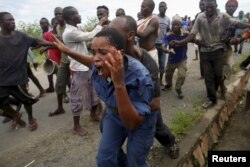 FILE - Protesters attack a policewoman in Bujumbura, Burundi, May 12, 2015, in a rally sparked by opposition to the president's decision to run for a third term.