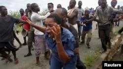 Những người biểu tình tấn công nữ cảnh sát ở Bujumbura, Burundi, ngày 12/5/2015, trong cuộc biểu tình chống lại quyết định tranh cử nhiệm kỳ thứ 3 của tổng thống.