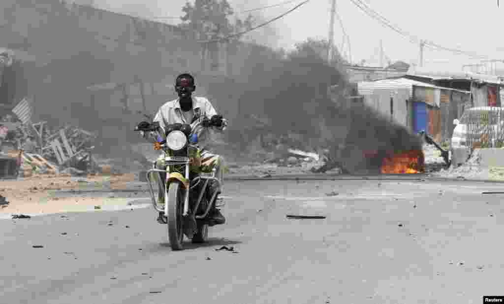 A motorcyclist rides away from the scene of an explosion near the entrance of the airport in Somalia's capital Mogadishu, Feb. 13, 2014.