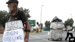 FILE - A man, left, begs, as another collects recyclable materials, at a street intersection in Johannesburg, South Africa, March 16, 2016.