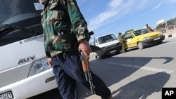 A militant with the Free Syrian Army walks in the northwestern city of Idlib, February 21, 2012.