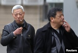 FILE - Smokers are seen on a street in Shanghai, China, March 22, 2012.