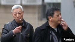 FILE - Smokers in a street in Shanghai, China, March 22, 2012.