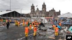 Para petugas kebersihan membersihkan lapangan Zocalo di Mexico City, pasca dibubarkannya aksi mogok ribuan guru oleh polisi huru-hara ibukota Meksiko tersebut, Jumat (13/9).