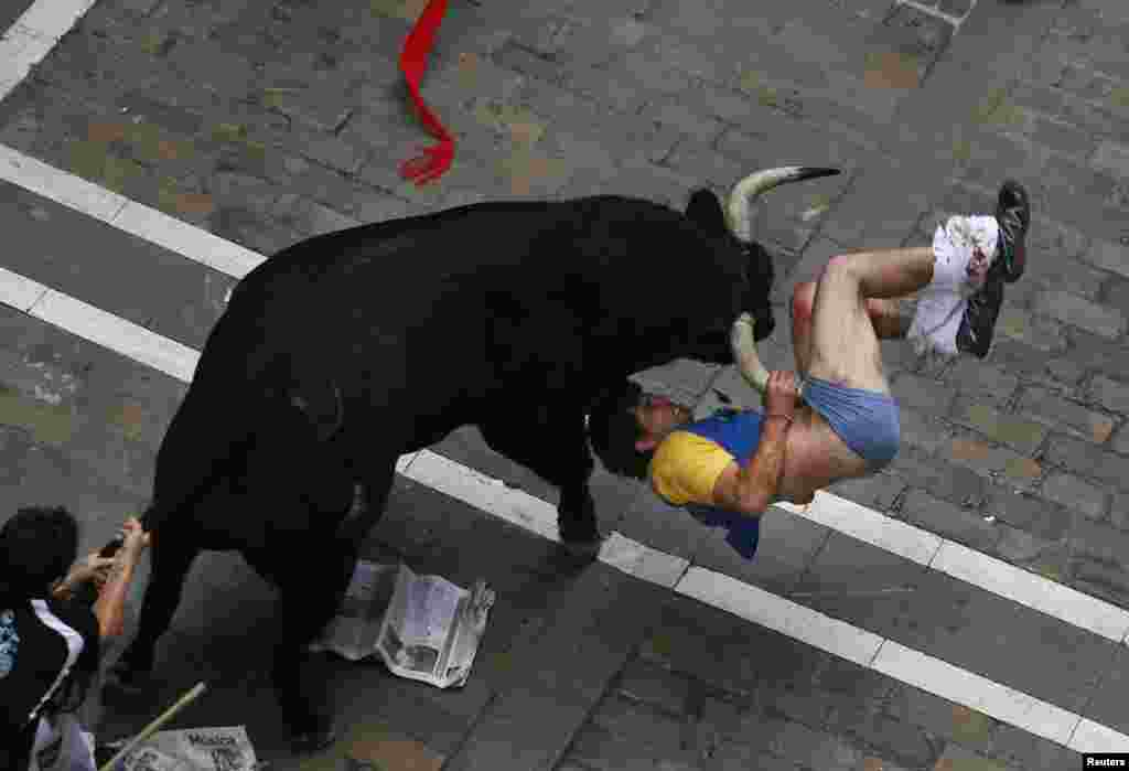 A runner is gored by an El Pilar fighting bull on Estafeta street during the sixth running of the bulls of the San Fermin festival in Pamplona, Spain, July 12, 2013.