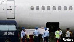 ទាហានឥណ្ឌូនេស៊ី និងក្រុមជួយសង្រ្គោះរៀបចំដាក់មឈូសអ្នកដំណើរមួយក្នុងជើងយន្តហោះ AirAsia QZ8501 ចូលទៅក្នុងផ្នែកមួយនៃយន្តហោះនៃក្រុមហ៊ុន Trigana នៅមូលដ្ឋានទ័ពអាកាស Iskandar។