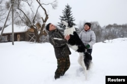 Dmitry Shamovich and his wife, Anastasia Kuzmenkova, play with the dog Amur at their homestead Zaimka Leshego in the village of Sosnovy Bor, Belarus, Feb. 7, 2018.