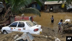 Residents stand in floodwaters after flash floods brought by Typhoon Washi (Sendong) hit Iligan city, southern Philippines December 17, 2011.