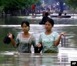 ພະນັກງານຍິງມຽນມາສອງຄົນ ຍ່າງລຸຍ ນໍ້າຖ້ວມທີ່ເມືອງ Mandalay, ມຽນມາ. (AP Photo)
