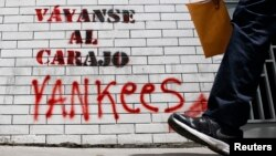 "A man walks past graffiti which reads ""Yankees, go to hell"" in Caracas, March 10, 2015."
