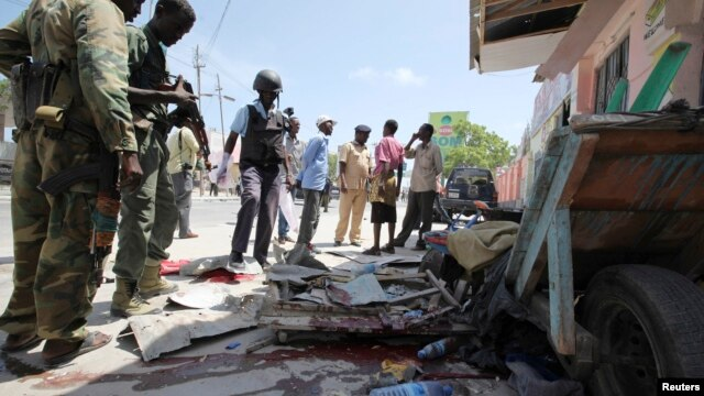 Somali soldiers stand at the scene of an explosion in the capital Mogadishu, May 3, 2014.