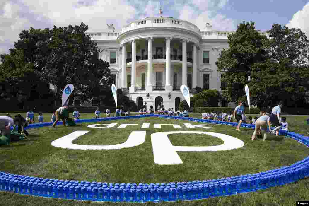 """U.S. First Lady Michelle Obama (C) and the Partnership for a Healthier America show a giant """"Drink Up"""" logo, as part of the """"Drink Up"""" campaign aimed at encouraging people to drink more water, on the South Lawn of the White House in Washington, July 22, 2014."""