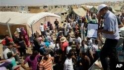 지난 13일 이라크 북부 다쿠르의 난민 난민촌에 서, 식량 지원을 받기 위해 모여든 시리아 난민들.