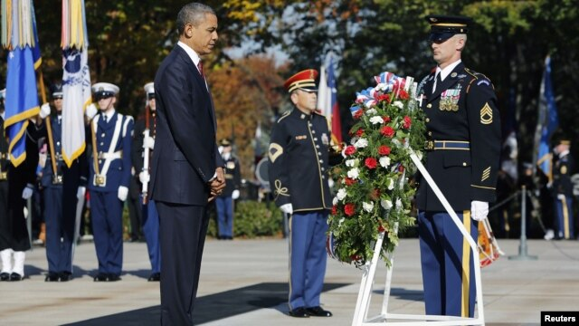 President Barack Obama (L) is seen after placing a Veterans Day wreath at the Tomb of the Unknowns at Arlington National Cemetery in Arlington, Virginia, November 11, 2012.