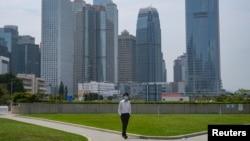 一名戴著口罩的男子行走在空空蕩蕩的香港金融區。 (2020年3月27日)