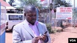 Ông Gerald Businge đang giải thích về ứng dụng Action for Transparency bên ngoài một trường học ở Kampala 2/7/2014. (Hilary Heuler/VOA)