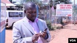 Gerald Businge demonstrates the Action for Transparency app, Kampala, July 2, 2014. (Hilary Heuler/VOA)