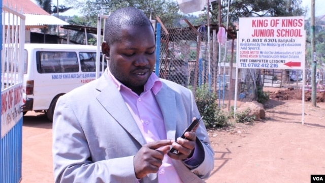Gerald Businge demonstrates the Action for Transparency app, Kampala, July 2, 2014. (Hilary Heuler/VOA)