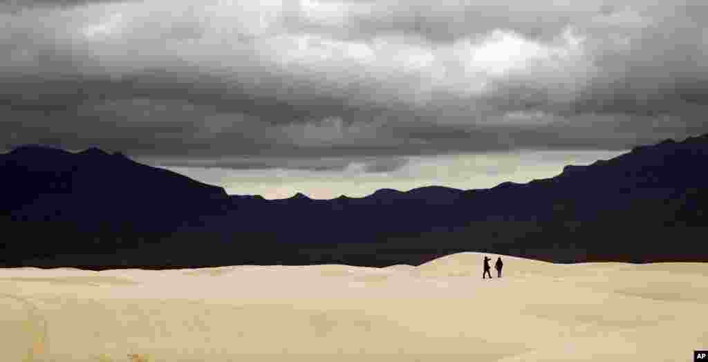 Visitors walk across dunes at White Sands National Monument as a rain storm passes, Feb. 10, 2019, near Alamogordo, New Mexico.