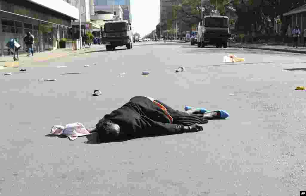 A woman lies in the road after been injured by police during protests in Harare.