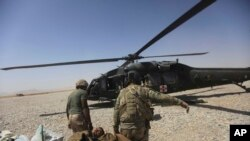 FILE - A U.S. Army medics carry a wounded soldier in Afghanistan's Helmand province Sept. 6, 2011. Two U.S. soldiers were among those killed and two were wounded when they came under enemy fire in Kunduz province, Afghanistan, the U.S. military said Thursday.