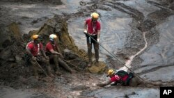Rescue workers take a rest from their search for victims at the town of Bento Rodrigues, after a dam burst on Thursday, in Minas Gerais state, Brazil, Nov. 8, 2015.