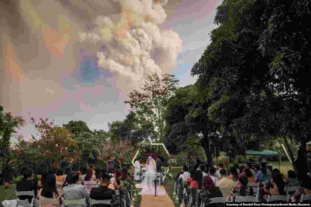 People attend a wedding ceremony as Taal Volcano sends out a column of ash in the background in Alfonso, Cavite, Philippines, in this image obtained from social media.