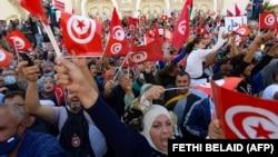 Des Tunisiens brandissent le drapeau national lors d'une manifestation contre le président Saied le long de l'avenue Habib Bourguiba dans la capitale Tunis, le 10 octobre 2021.