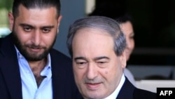 FILE - Syrian Deputy Foreign Minister Faisal Mekdad (R) leaves the hotel, where the team of chemical experts from the Organization for the Prohibition of Chemical Weapons (OPCW) are residing, on April 15, 2018, in Damascus.