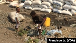 Meninos apanham garrafas de plástico vazias na estação de Caminhos de Ferro de Moçambique em Moatize