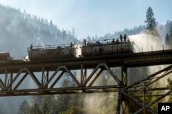 Petugas pemadam kebakaran menyemprotkan air dari kereta api Union Pacific Railroad saat memadamkan Dixie Fire di Hutan Nasional Plumas, California, Jumat, 16 Juli 2021. (AP Photo/Noah Berger)
