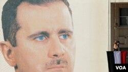 Seorang Pro-rejim Suriah menggelar aksi pertunjukan dengan menggelantungkan diri sambil memegang bendera kebangsaannya di depan gambar raksasa presiden Suriah Bashar al-Asaad di Damaskus (2/12).