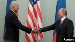FILE - Russian Prime Minister Vladimir Putin (R) shakes hands with then-U.S. Vice President Joe Biden during their meeting in Moscow March 10, 2011.
