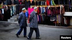 FILE - Two ethnic Uighur men walk in a clothing market in downtown Urumqi, Xinjiang province.