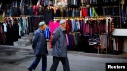 دو مرد اویغوری در بازار پوشاک ارومچی قدم می زنند