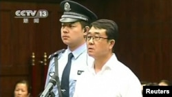 Chongqing municipality ex-police chief Wang Lijun (R) reads a statement during his sentencing inside the courtroom of the Chengdu People's Intermediate Court in Chengdu, Sichuan province in this still image taken from video, Sept. 24, 2012.