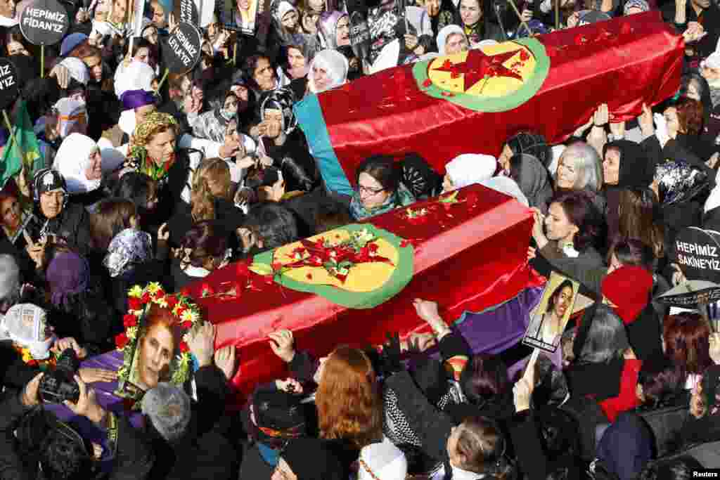 People carry the coffins of the Kurdish activists who were shot in Paris, during a funeral ceremony in Diyarbakir, Turkey, January 17, 2013.