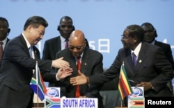 FILE - China's president, Xi Jinping, left, shakes hands with the former president of Zimbabwe, Robert Mugabe, right, while South Africa's former President Jacob Zuma looks on during a Forum on China-Africa Cooperation in Sandton, Johannesburg, Dec. 4, 2015.
