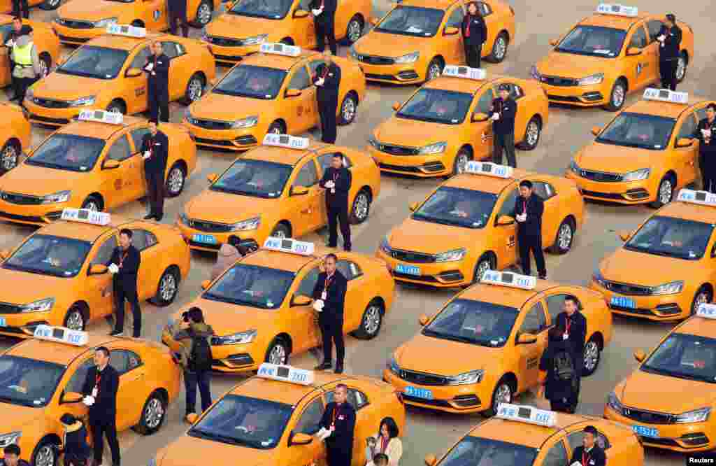 People attend an unveiling ceremony for a fleet of new methanol-fueled taxis, developed by Geely, in Xian, Shaanxi province, China. (Stringer Network)