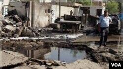Polisi Irak memeriksa lokasi pemboman bunuh diri di depan kantor polisi di Baghdad, Rabu (12/10).